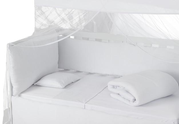 Белая детская кроватка с подушкой, пуховым одеялом и мушкетером, изолированными на белом фоне. детальный вид.