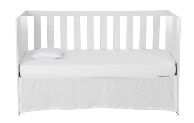 Белая детская кроватка с подушкой, изолированной на белом фоне.
