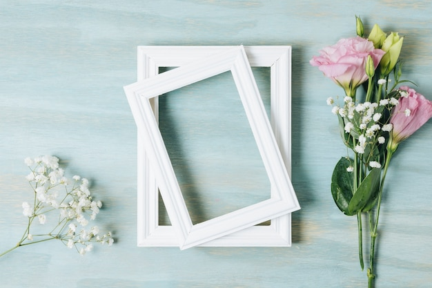 White baby's-breath flower and eustoma near the wooden white frame on blue texture backdrop