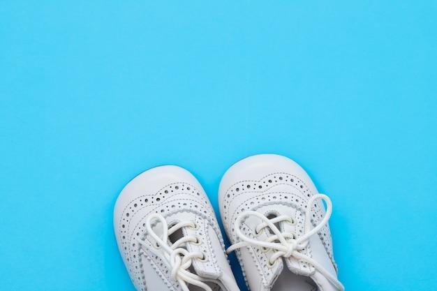 Белая детская обувь на синем фоне