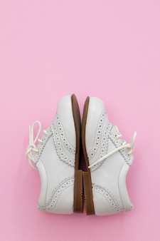 분홍색 종이 배경에 흰색 아기 신발