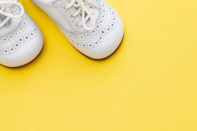 黄色の背景に白いベビーシューズ