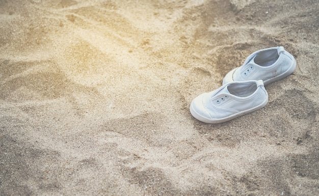 白いベビースニーカー砂浜で