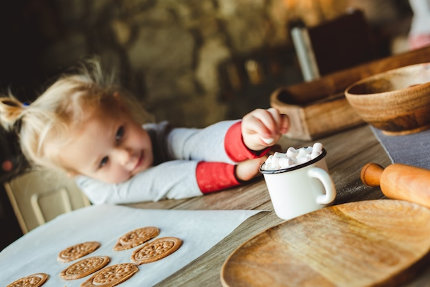 White baby in traditional pyjamas takes marshmallows from a cup of cocoa.