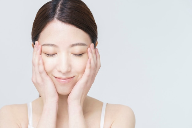 白い背景の美しさの画像/彼女の顔に触れるアジアの女性
