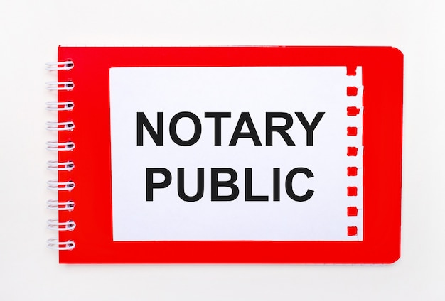On a white background - a bright red notebook on a spiral. on it is a white sheet of paper with the text notary public