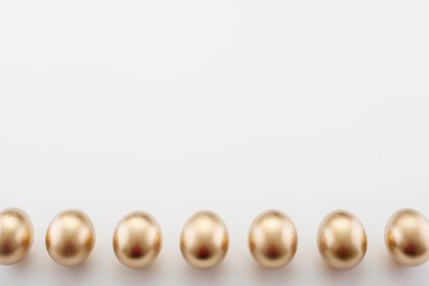 コピースペースと、黄金の卵で飾られたイースターの白い背景。