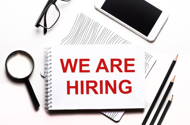 On a white background glasses, a magnifier, pencils, a smartphone and a notebook with the text we are hiring