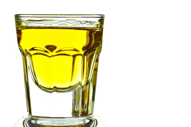 On a white background on the left side of a glass with whiskey close-up. on the right is an empty space for an inscription