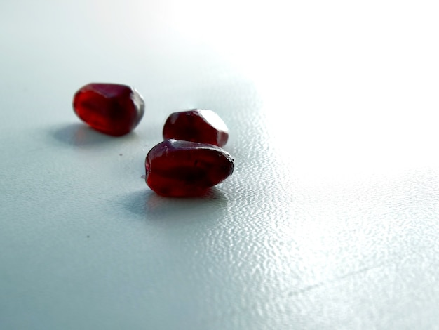 On a white background red pomegranate seeds