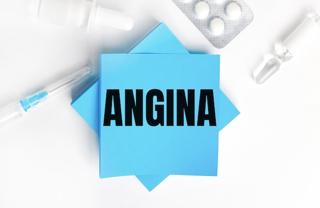 On a white background, a syringe, ampoule, pills, a vial of medicine and light blue stickers with the inscription angina