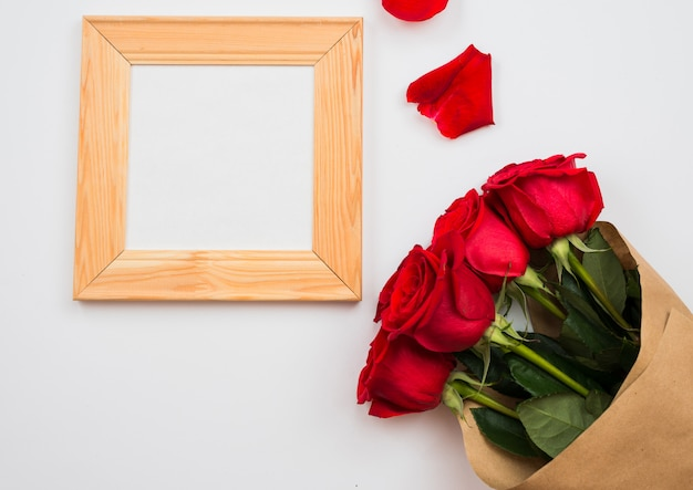 On a white background there are beautiful red roses and a frame. place for text, copy space