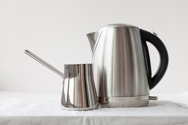 On a white background there is an iron electric kettle and an iron turk. coffee making concept, good morning, breakfast, dishes.