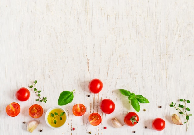 White background with cherry tomatoes, basil leaves and olive oil