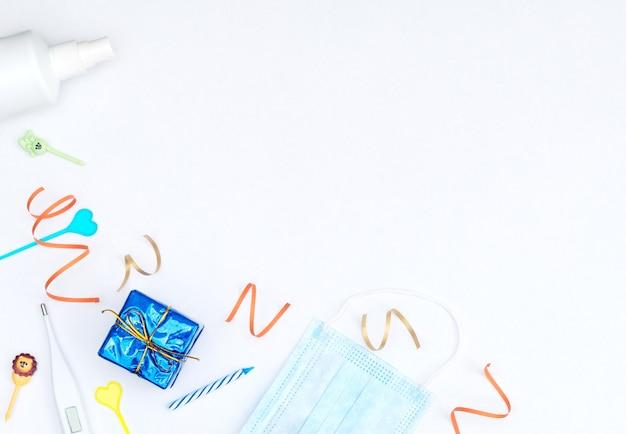 Белый фон с подарочной коробкой, растяжки, свечи, медицинская маска для лица, термометр, дезинфицирующее средство.