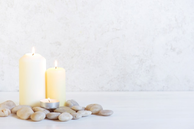 White background with three burning candles and stones