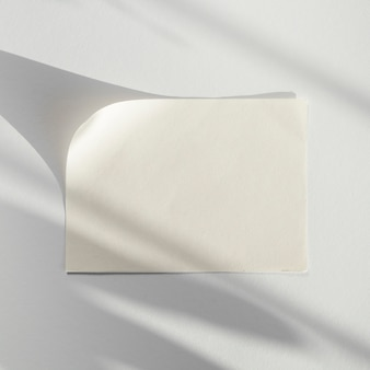 Sfondo bianco con un bianco bianco di carta con la sua ombra