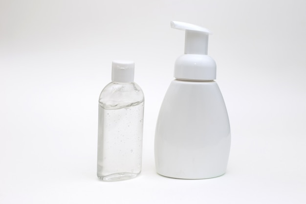 White background with a white bottle of antibacterial soap and bottle antibacterial gel for hands