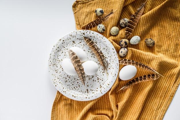 Белый фон с белыми яйцами и перьями. белый фон. вид сверху.