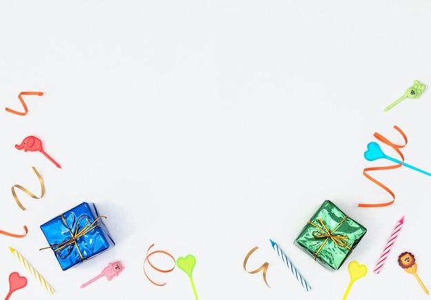 Белый фон с обернутыми подарочными коробками, растяжками, свечами и шпажками.