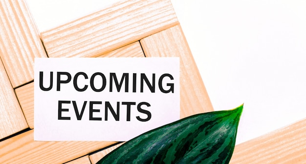 On a white background wooden building blocks, a white card with the text upcoming events and a green leaf of the plant. view from above