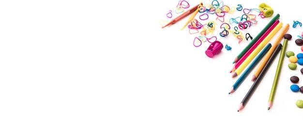 カラフルな子供のお菓子とコピースペースの子供時代のコンセプトの文房具と白い背景