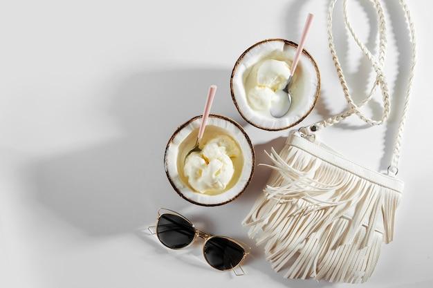 ココナッツの半分に白いバッグとアイスクリーム。夏休みのコンセプト。