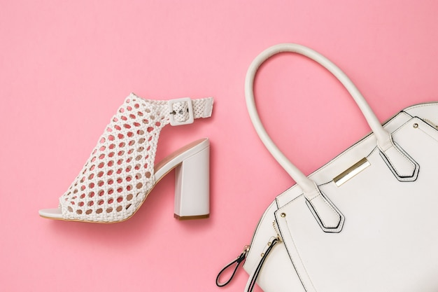 White bag with black trim and white summer shoes on pink surface
