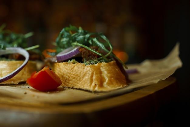 허브와 붉은 양파 링과 레스토랑에서 나무 보드에 붉은 신선한 토마토 조각 고기 페이트와 흰색 바게트 샌드위치. 건강하고 맛있는 음식. 확대