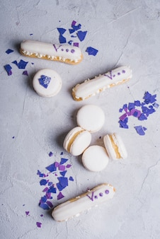 White baked macaroons and eclairs on concrete textured background