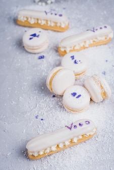 White baked macaroons and eclairs dusted with desiccated coconut on textured background