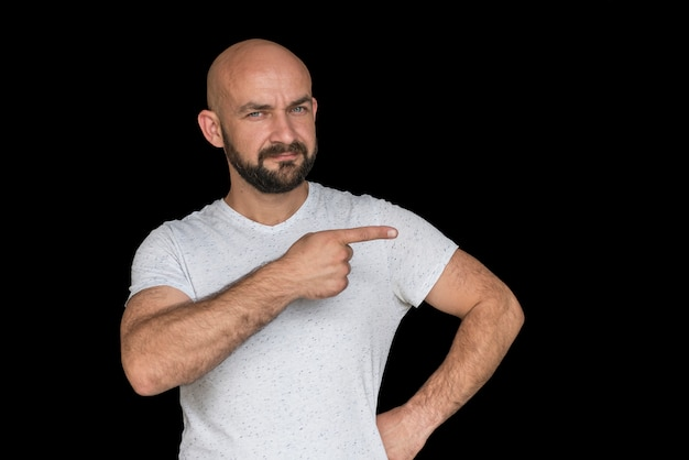 White bald man with a beard in a white t-shirt points finger to the side