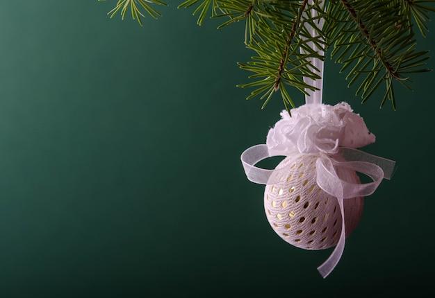 緑のクリスマスツリーの枝にぶら下がっている白いボール