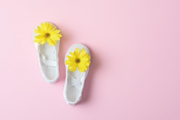 コピースペースのあるピンクのテーブルに黄色い花が咲く白いバレエシューズ。