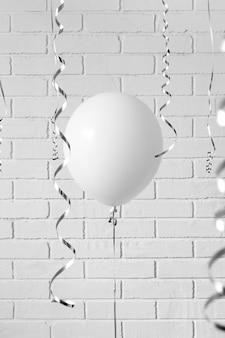 灰色のレンガの壁に白い風船。概念