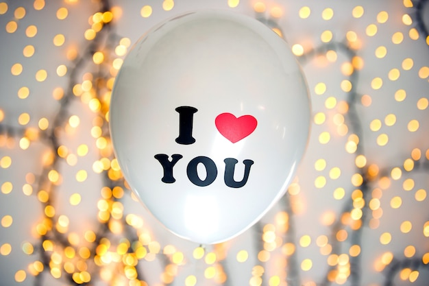 White balloon with i love you written on with sparkling bokeh