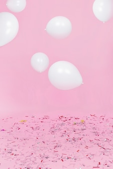 White balloons in air over the confetti against pink background