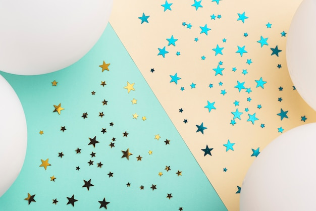 White balloons and confetti stars on colorful background