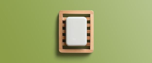 녹색 배경에 나무 접시에 비누의 흰색 바. 바로 위, 복사 공간.