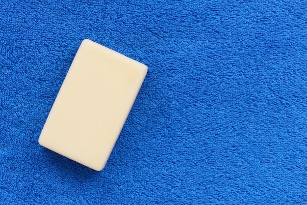 コピースペース、衛生コンセプトとふわふわの素朴なタオルブルーの石鹸の白いバー