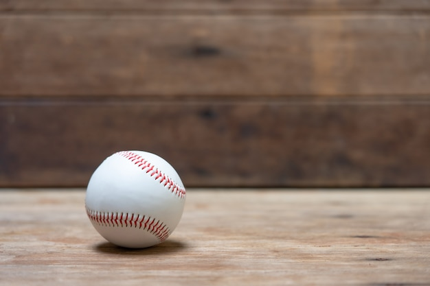 White baseball with red thread on wood