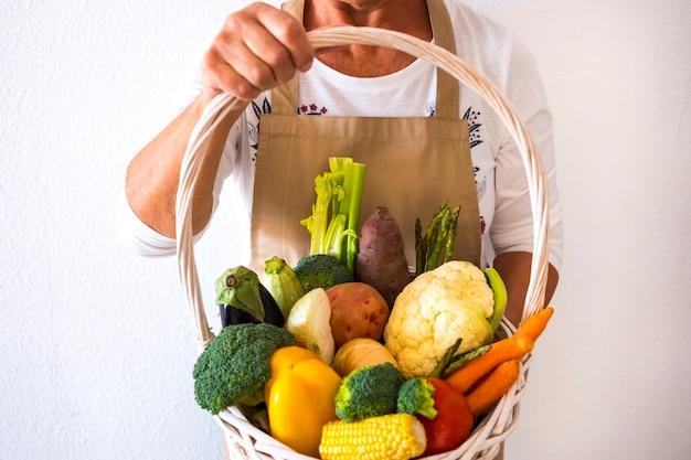 新鮮で健康的な野菜でいっぱいの人間の女性の手の白いバスケット