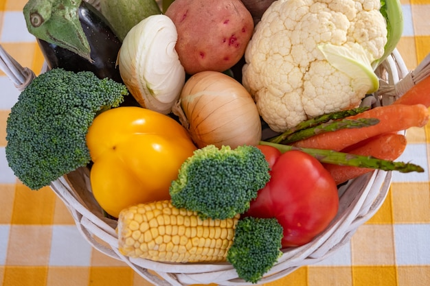 White basket with fresh vegetables broccoli pepper cauliflower tomatoes healthy eating concept