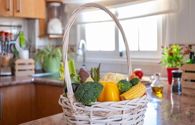 キッチンに新鮮な野菜が入った白いバスケット健康的な食事のコンセプトとデトックスダイエット