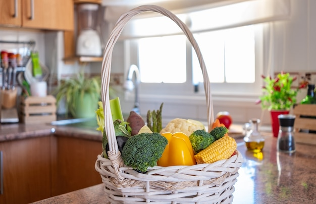 White basket with fresh vegetables in the kitchen healthy eating concept and detox diet