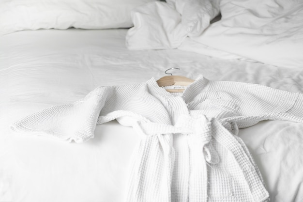 White bath robe on the bed in hotel room