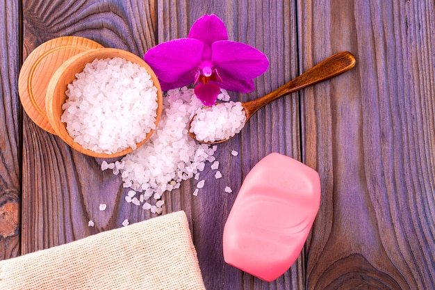 蘭、黄麻布、石鹸のバーが付いた木製のテーブルにスプーンで木製カップの白いバスソルト。