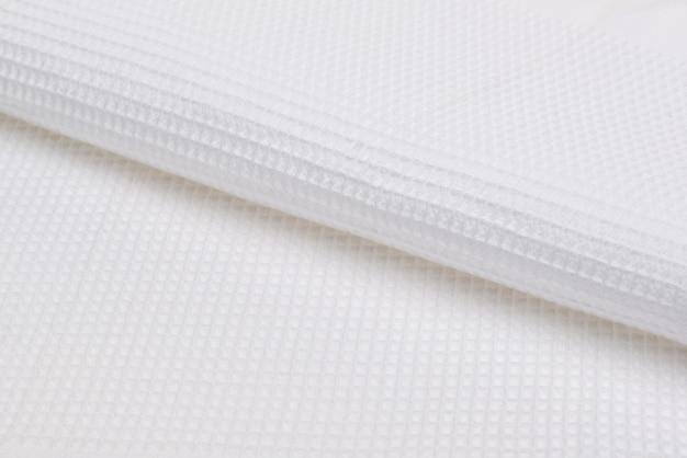 白いバスタオル。テクスチャード生地の背景