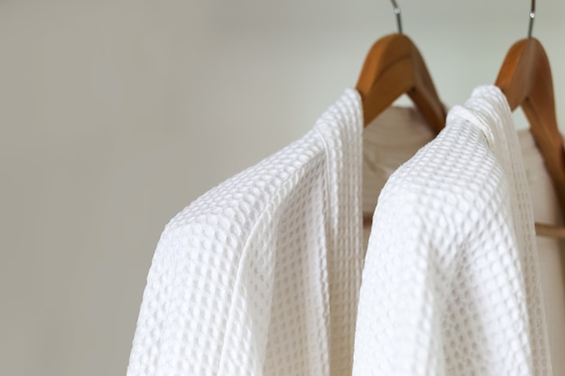 White bathrobe hanging on rack