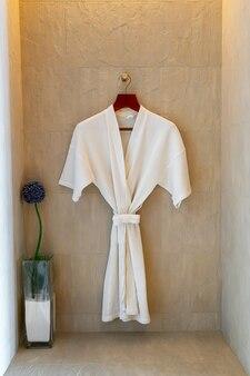 White bathrobe hanging on wall in bathroom